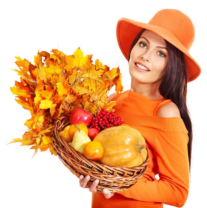 Woman holding autumn basket with fruit and vegetable. Isolated.