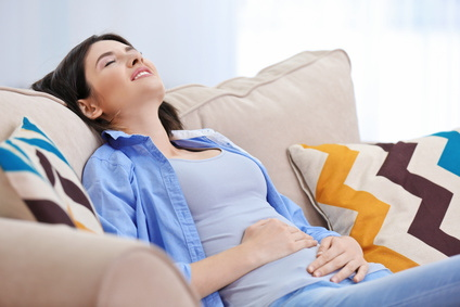 Beautiful young woman suffering from abdominal pain while sitting on sofa at home
